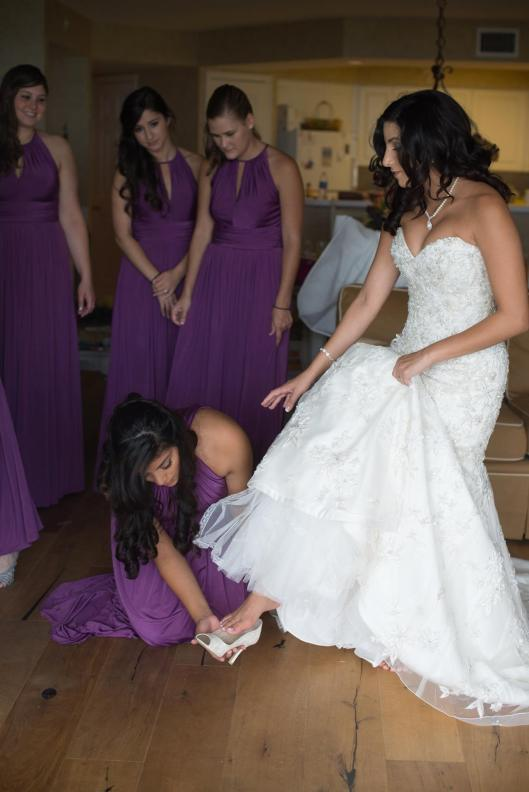 Bridesmaids helping the bride with her shoes